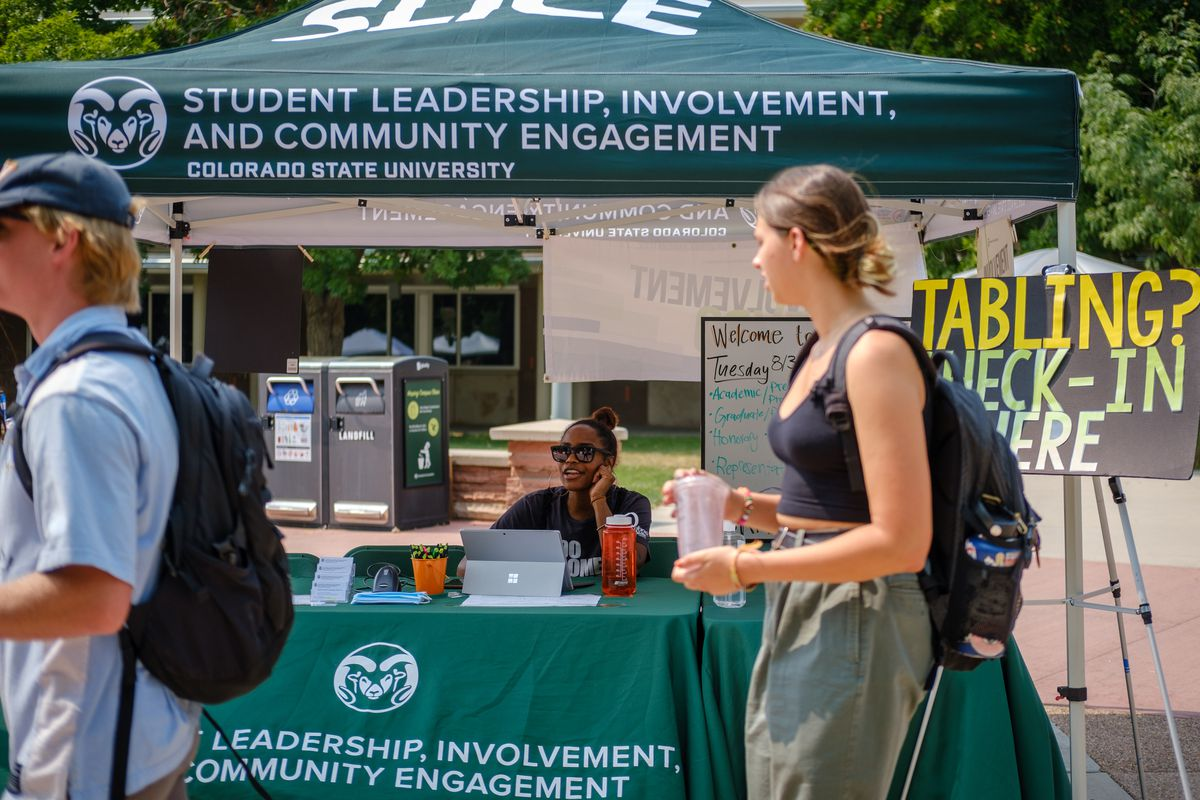 Students walk past a tent for Colorado State University's Student Leadership, Involvement, and Community Engagement tent during a student involvement fair.