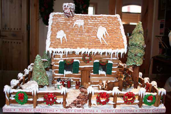 Gingerbread cabin with the words merry Christmas written around the outside.