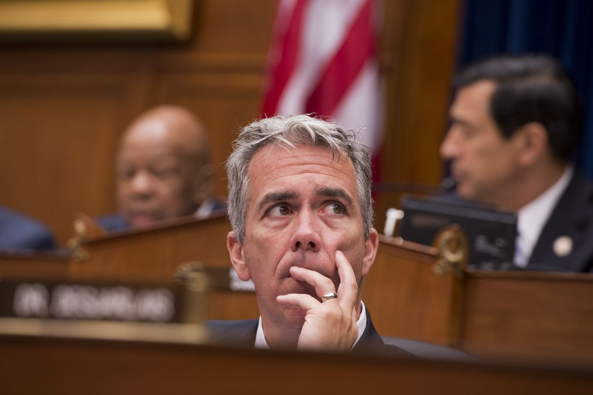 Representative Joe Walsh sitting in a House committee meeting with his hand holding his chin.