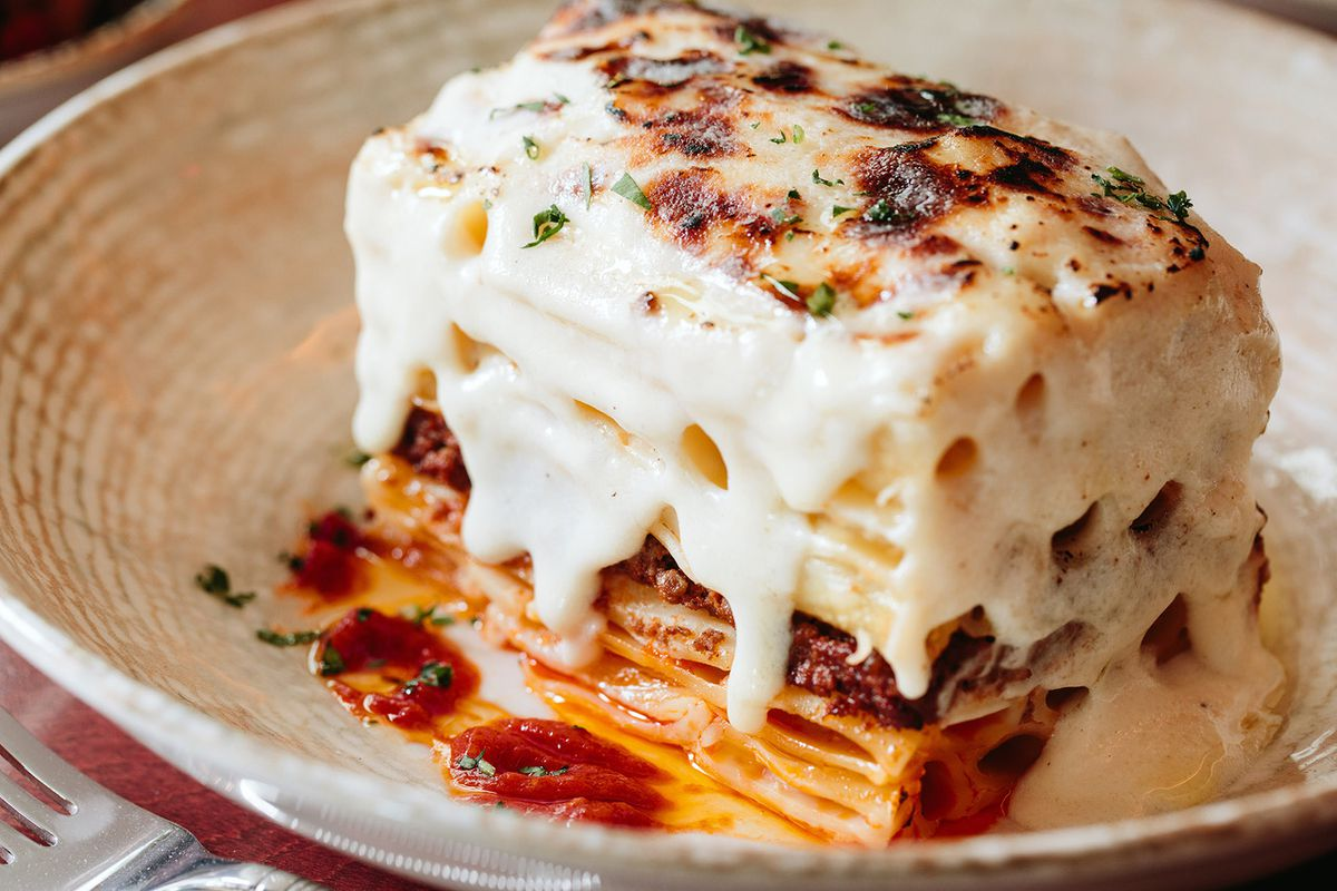 Closeup shot of a lasagna-like dish, pastitsio, dripping with a white sauce. The top is browned in the oven and sprinkled with green herbs.