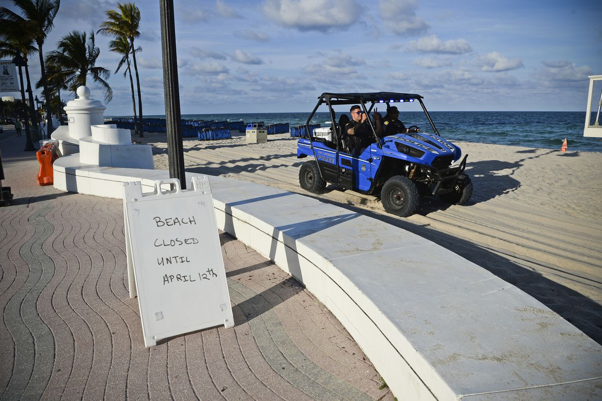 """A sand utility vehicle on the beach in Fort Lauderdale beside a sign that reads, """"Beach closed until April 12th."""""""