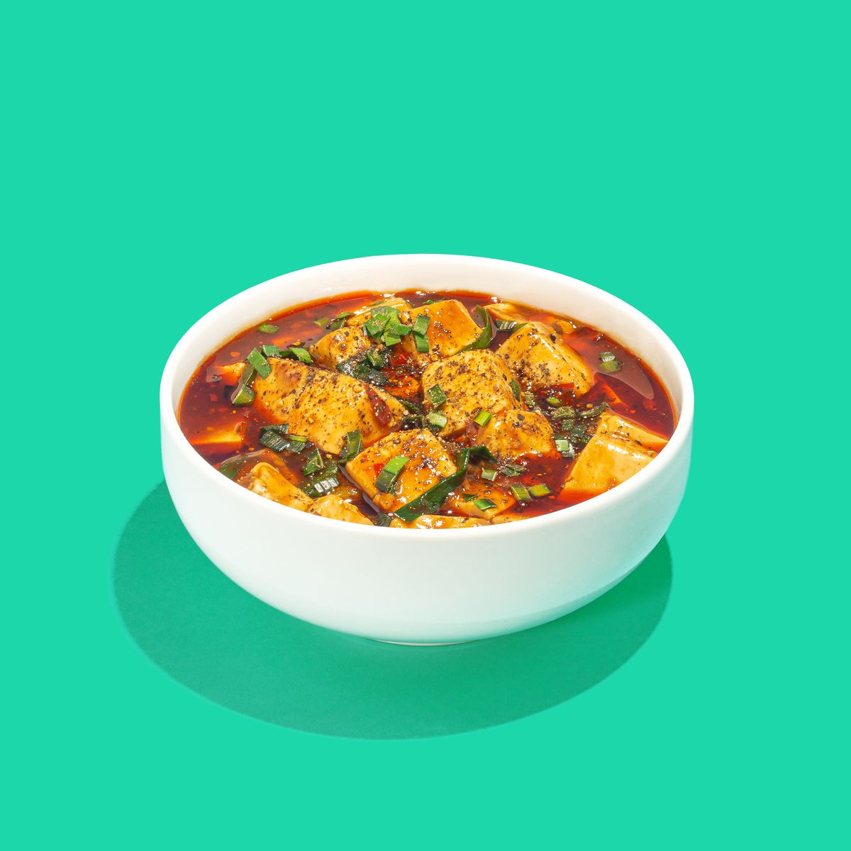 A white bowl against a green background with a reddish sauce and pieces of tofu in it