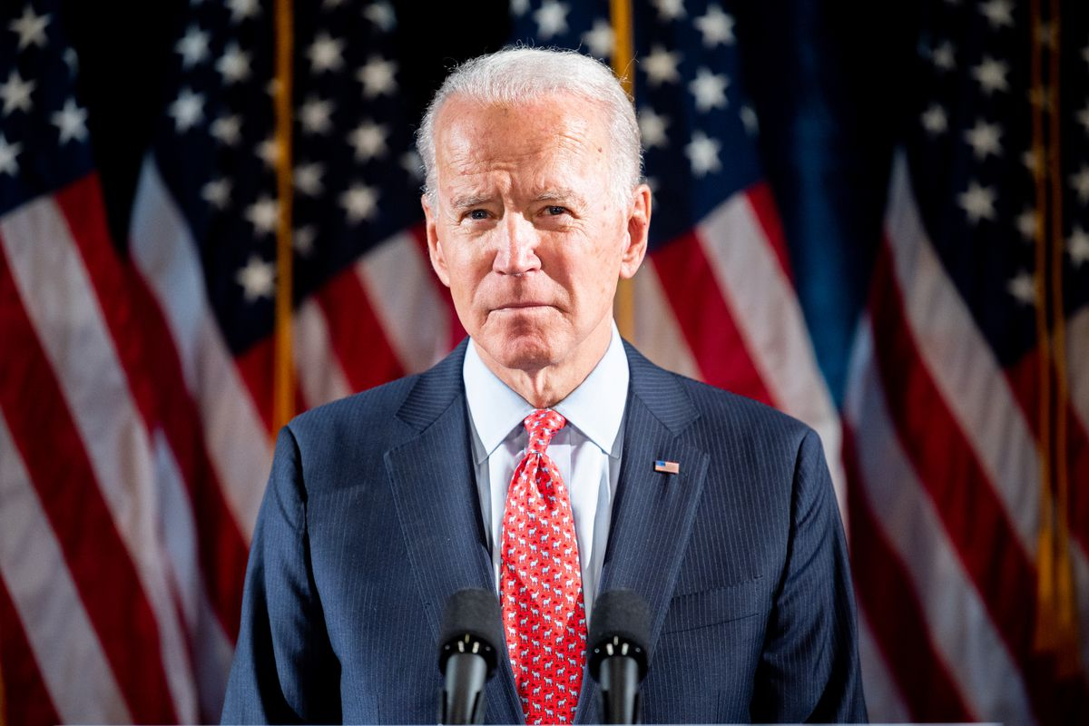Biden appears sober, brightly lit by stage lights, in a dark suit and red tie. He stands at a podium in front of a row of US flags.