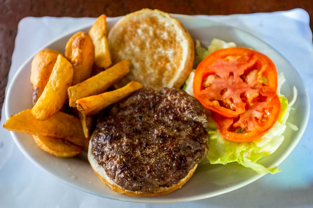 An open-faced burger, lettuce and tomato, and thick-cut wedge fries sit on a plate