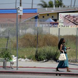 In this Tuesday April 17,2012 photo a woman walks past an empty lot on Vermont Ave. between 85th St. and Manchester Ave. in South Central Los Angeles. Several large stores once occupied the lot that was looted and set afire during the riots of 1992. Twenty years since the 1992 LA riots residents of the city's largely black and Hispanic South Side complain that the area still is plagued by too few jobs, too few grocery stores and a lack of redevelopment that would bring more life to the area.