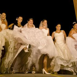 In this Sunday, Aug. 26, 2012 photo shot under iodine street lighting, Romanian brides pose for pictures under the Triumph Arch in Bucharest, Romania. The arch, a replica of the Arc de Triomphe in Paris, the French capital, is a rendezvous place for brides on the wedding night for the bride stealing ritual. The ancient Romanian tradition of bride stealing is getting bigger, brasher and an increasingly common sight in the Romanian capital, the region's undisputed party town.