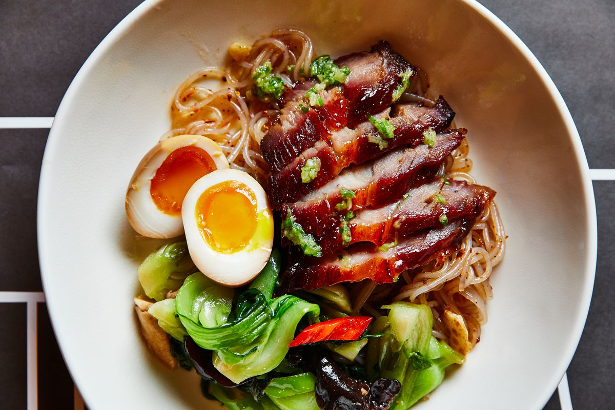 A white bowl filled with noodles, vegetables, and red barbecued pork plus a soft boiled egg