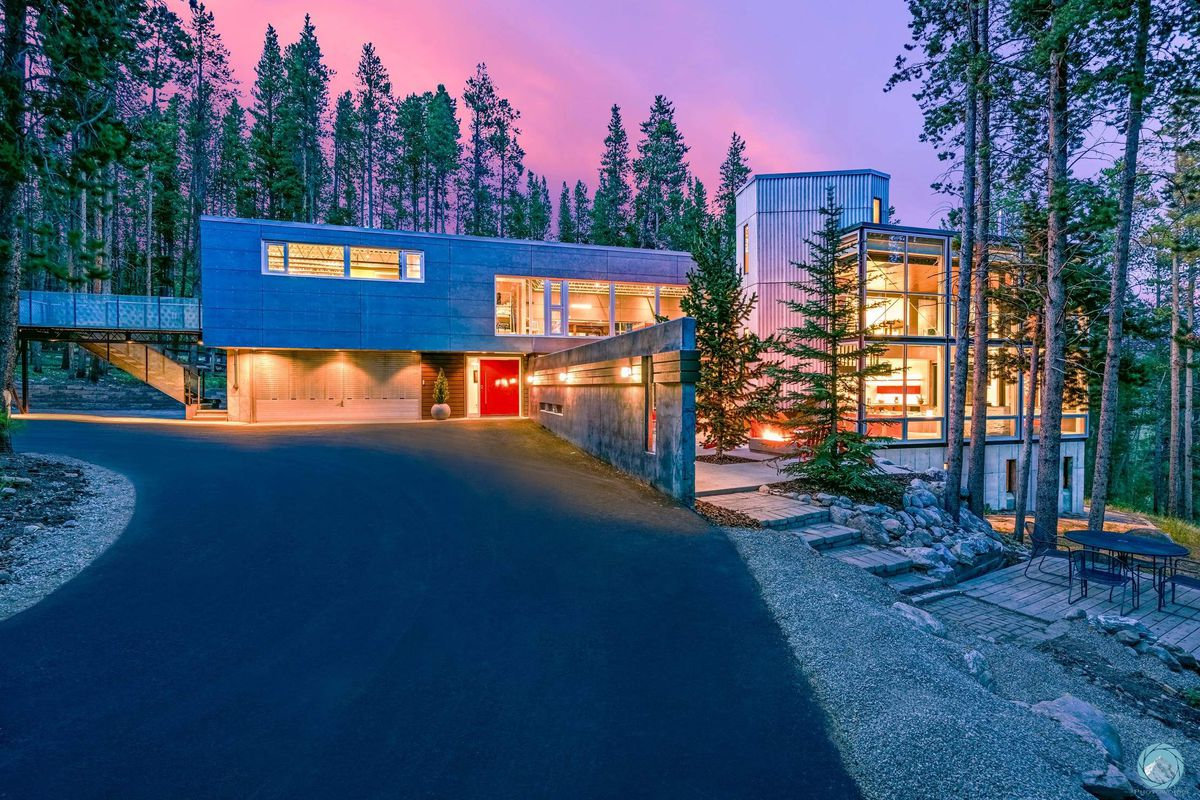 A silver, boxy modern house features a long driveway and lots of glass walls. Lights are on at sunset so the home appears to glow, and trees are in the background.