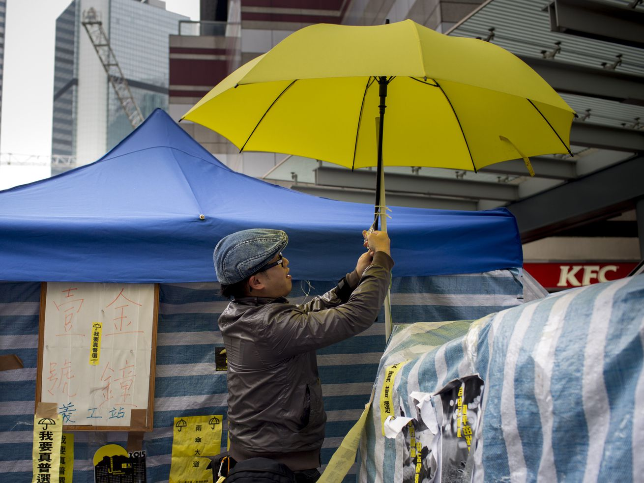 A pro-democracy protester cuts down a yellow umbrella outside Hong Kong's Government complex on December 11, 2014.