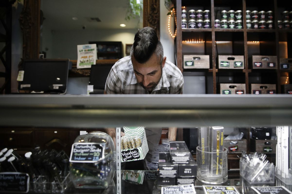 Jerred Kiloh, owner of the licensed medical marijuana dispensary Higher Path, stocks shelves with cannabis products in Los Angeles.