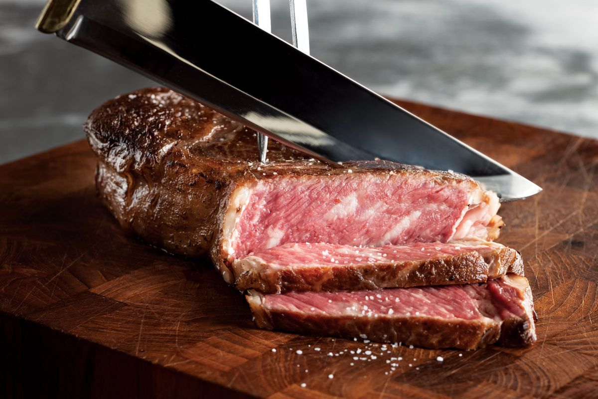 A piece of rare steak is on a wooden cutting board, partially sliced, as a sharp knife held out of frame makes the next slice