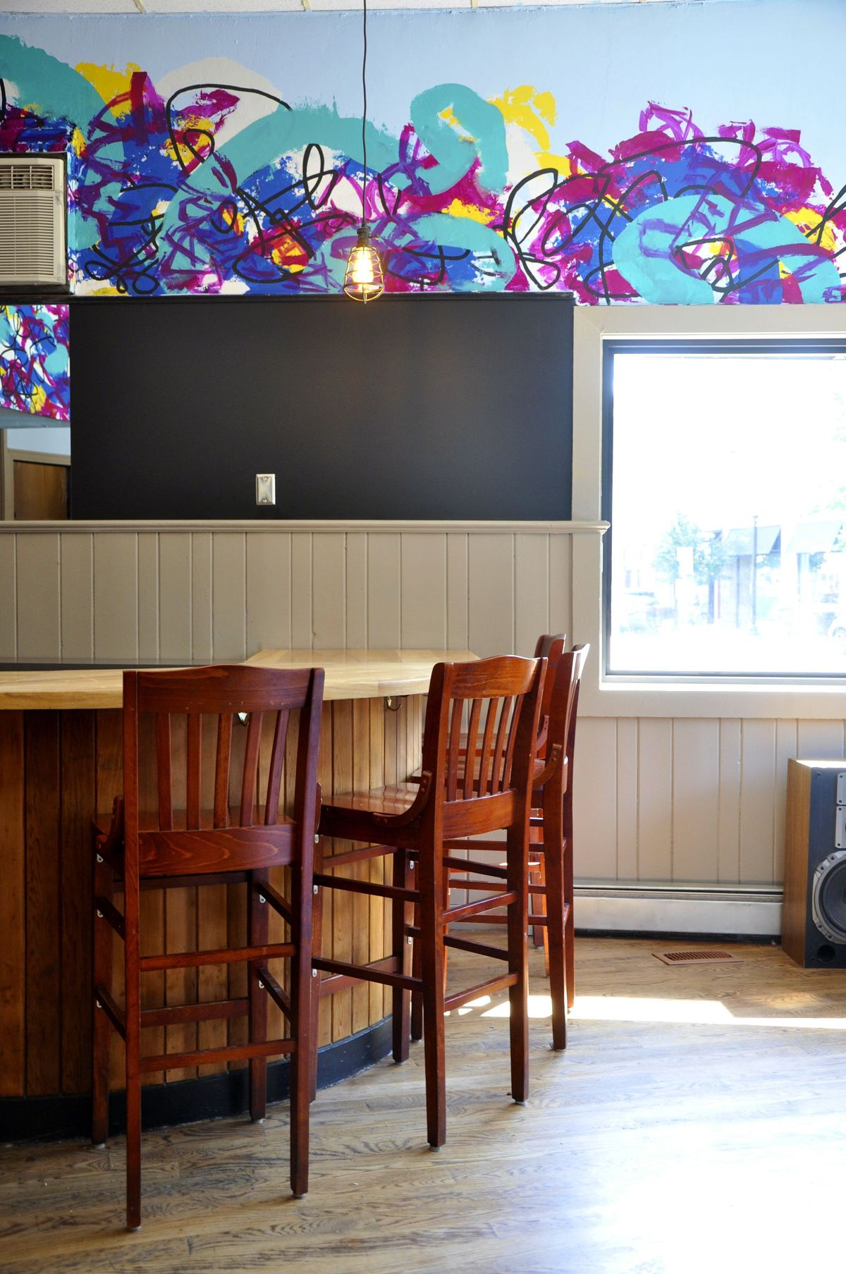 A wooden bar curves toward a wall painted black in part, with a colorful mural overhead