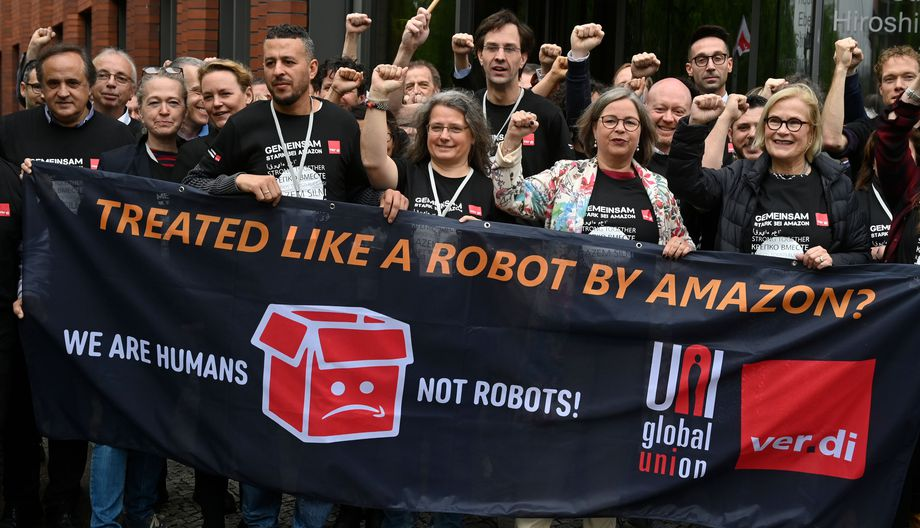 "Amazon workers in Germany hold a banner reading ""We are Humans not robots!"""