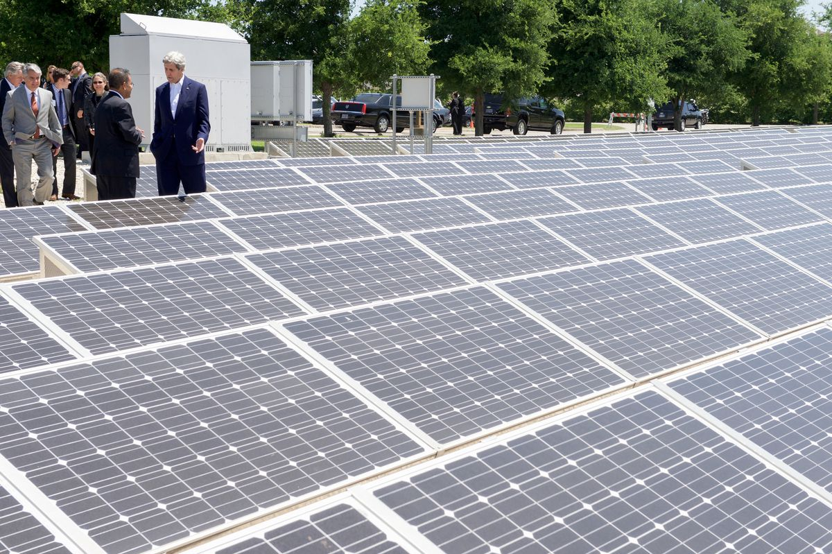 Former Secretary of State John Kerry talks solar research with Sanjay Banerjee, director of UT's Pickle Research Center in Austin—big solar field in front, trees in back