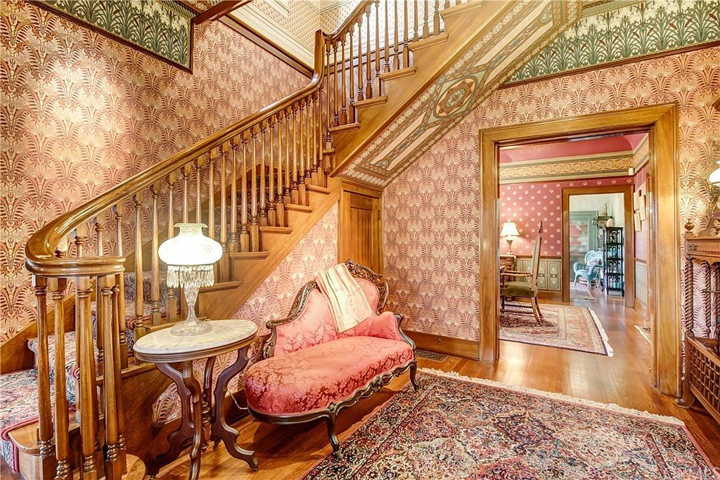 Entryway with curved staircase banister and patterned wallpaper.
