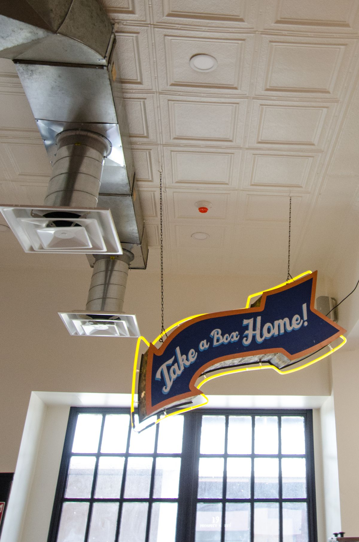 """A vintage-looking arrow-shaped sign has cursive text that says """"take a box home!"""" It hangs from the ceiling of a brightly lit restaurant in front of a large window"""