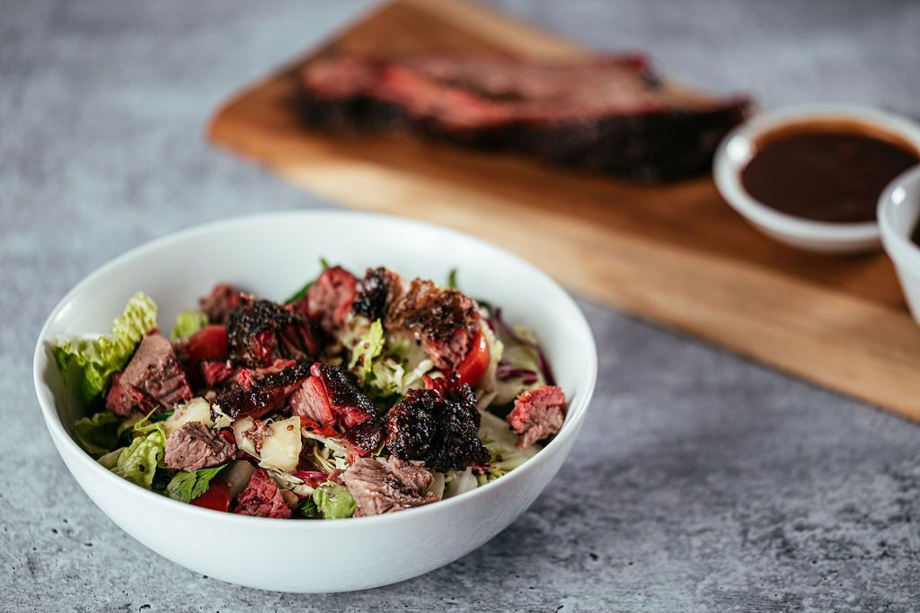 A salad with romaine and chopped meat with a rack of ribs on a cutting board in the background.