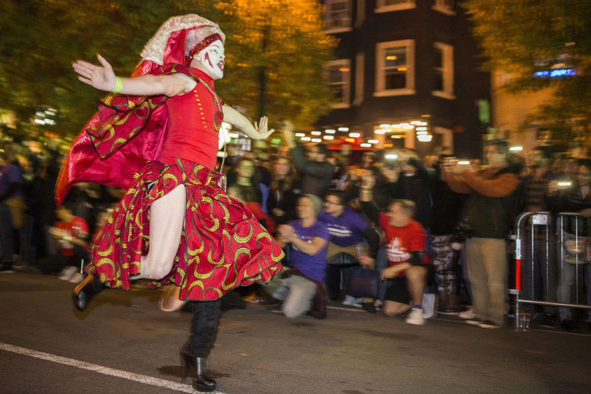 A person running with arms outstretched on a city street. The person is wearing a drag outfit: a red skirt and red top with a red veil. They wear white makeup.