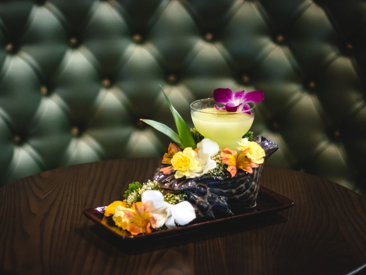 A frozen cocktail sits on a dark wooden table, garnished extensively with fresh flowers. A dark green leather booth is visible in the back.