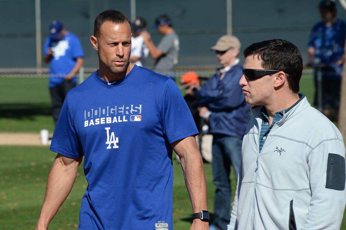 Gabe Kapler, left, talks with Andrew Friedman during spring training in 2015, as Ken Gurnick of MLB.com lurks in the background.