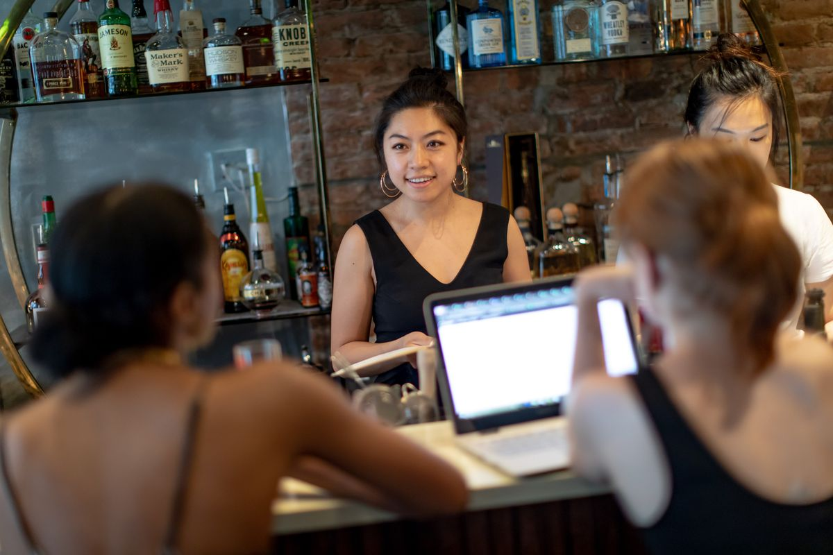 Amelie Kang talks to employees inside her restaurant