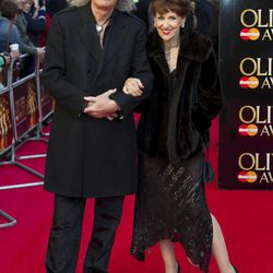 British musician Brian May, left, and British actress Anita Dobson arrive for the Olivier Awards at the Royal Opera House, London, Sunday, April 15, 2012.
