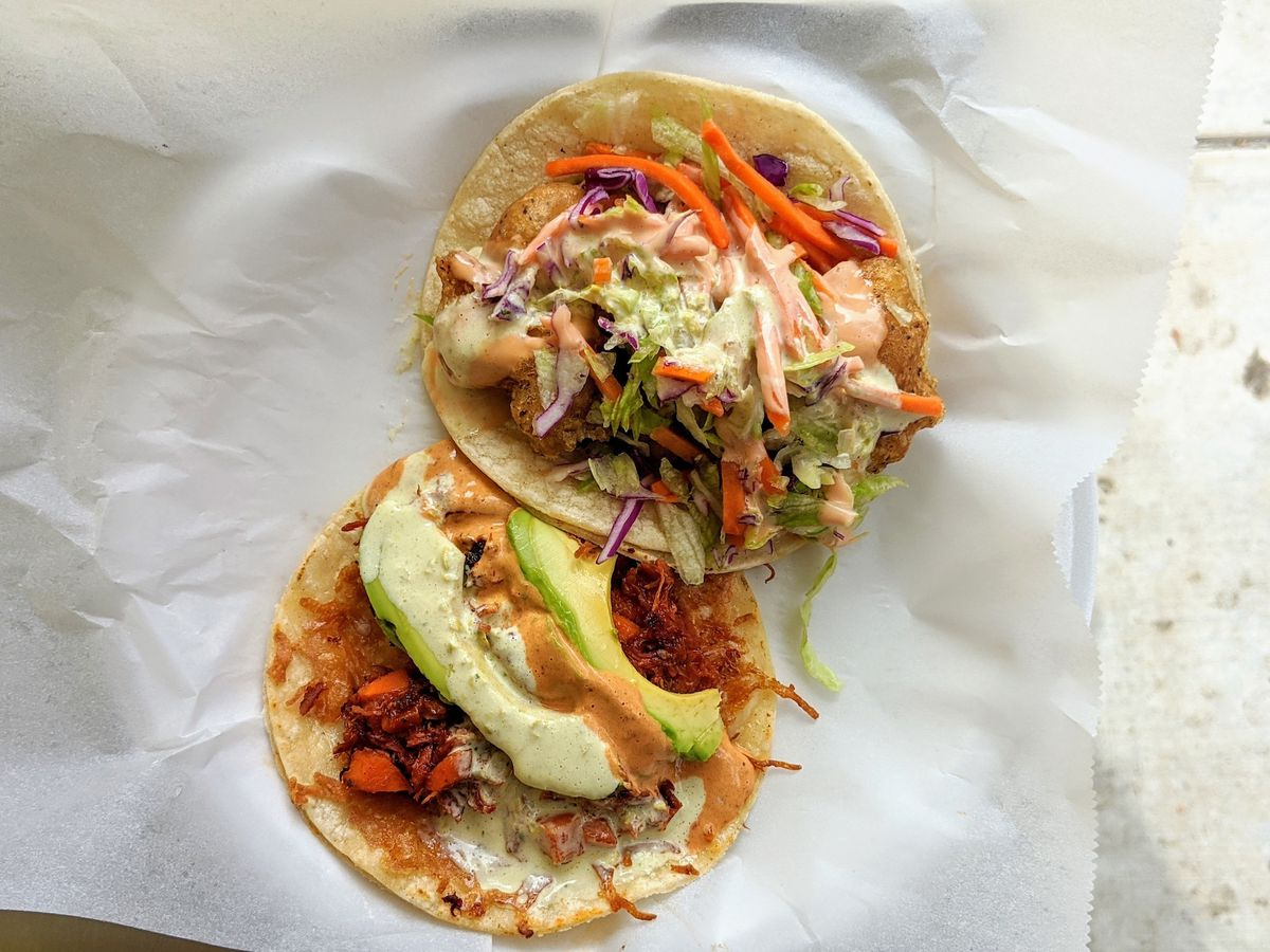 Two marlin tacos from above with avocado slices on corn tortillas.