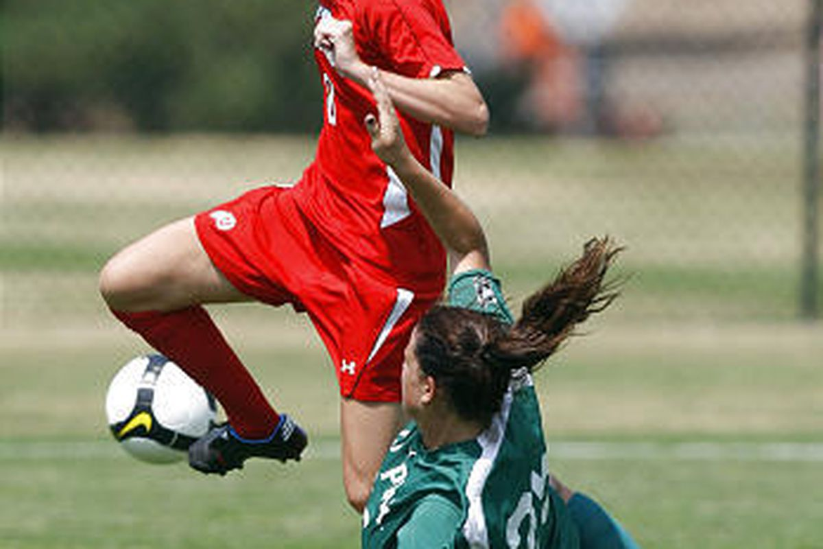 University of Utah's Erin Dalley, top, leaps over the slide tackle attempt of Cal Poly's Julianne Grinstead in the Utes' 2-0 win over the Mustangs at Ute Field Sunday afternoon.