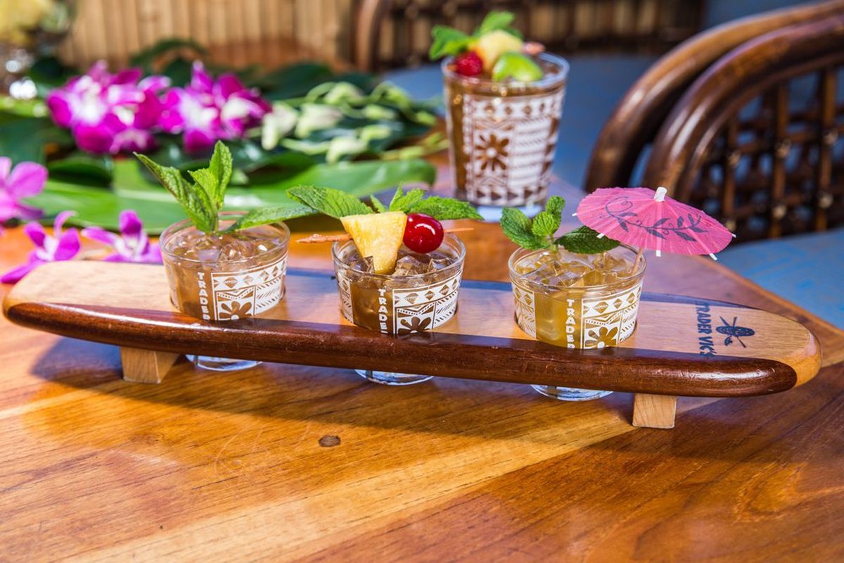 A flight of three mai tais on a small wooden surf board