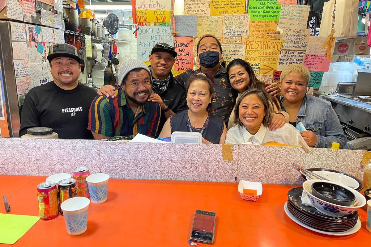 A group of smiling brown-skinned people stand together taking a mirror selfie. Hand-written signs and notices are posted on the wall behind them.