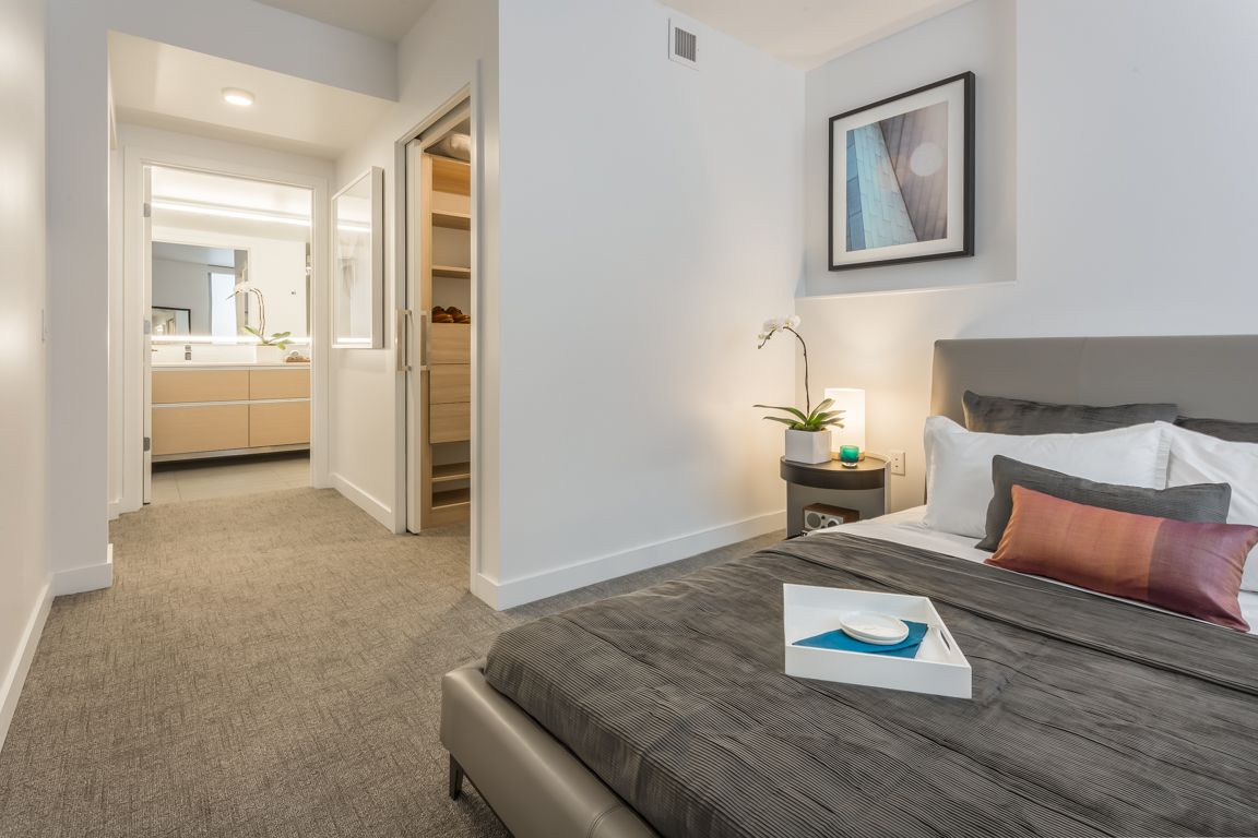 A bedroom with doors to a walk in closet and a master bath visible