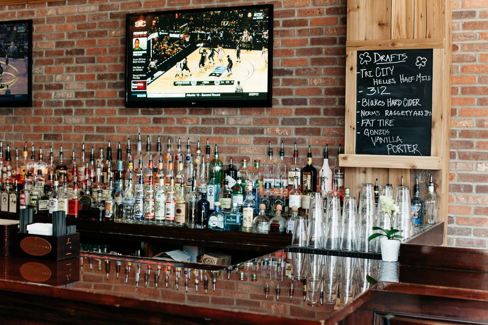 A TV hanging on a brick wall behind the bar at Cornerstone Barrel House is tuned in to a basketball game.