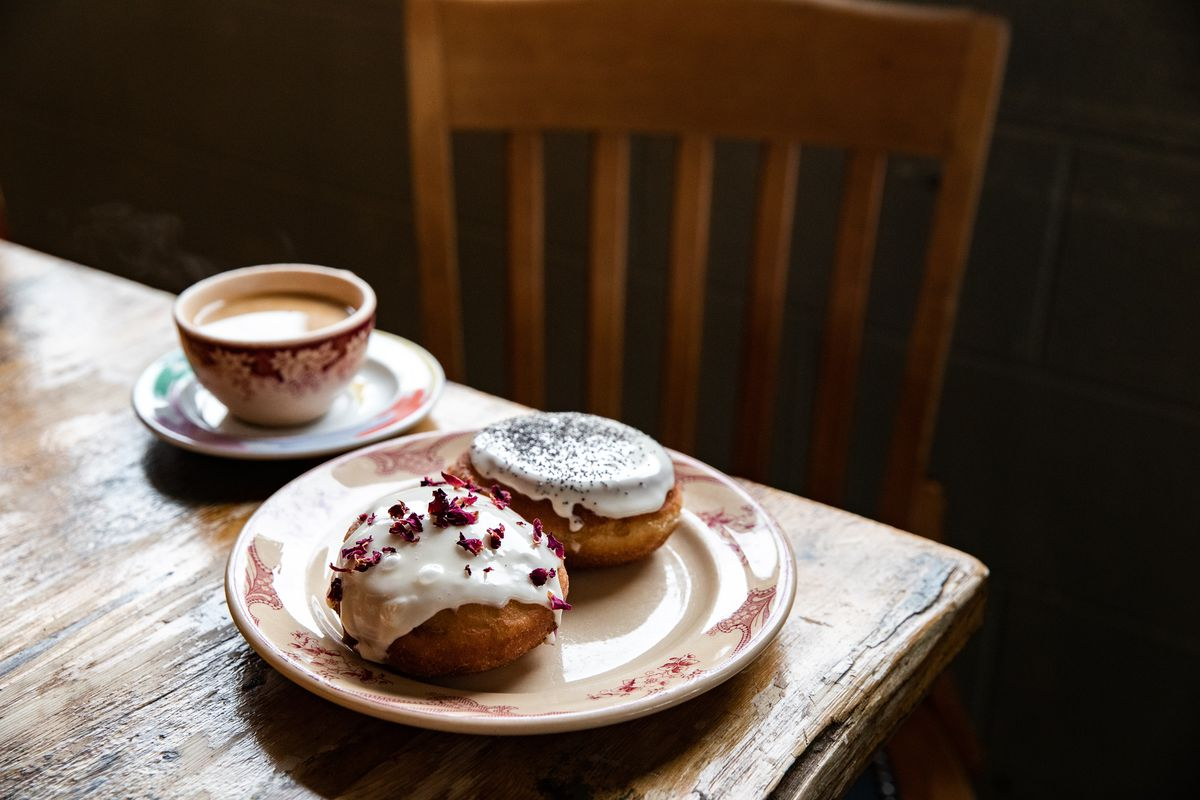 two paczki made with potato dough topped with icing and rose flowers and poppy seeds.  There's a cup of coffee next to them