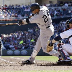 New York Yankees' Robinson Cano hits a two-run double in the third inning of a baseball game off Minnesota Twins pitcher Brian Duensing on Wednesday, Sept. 26, 2012 in Minneapolis. Catching is Twins' Ryan Doumit, right.