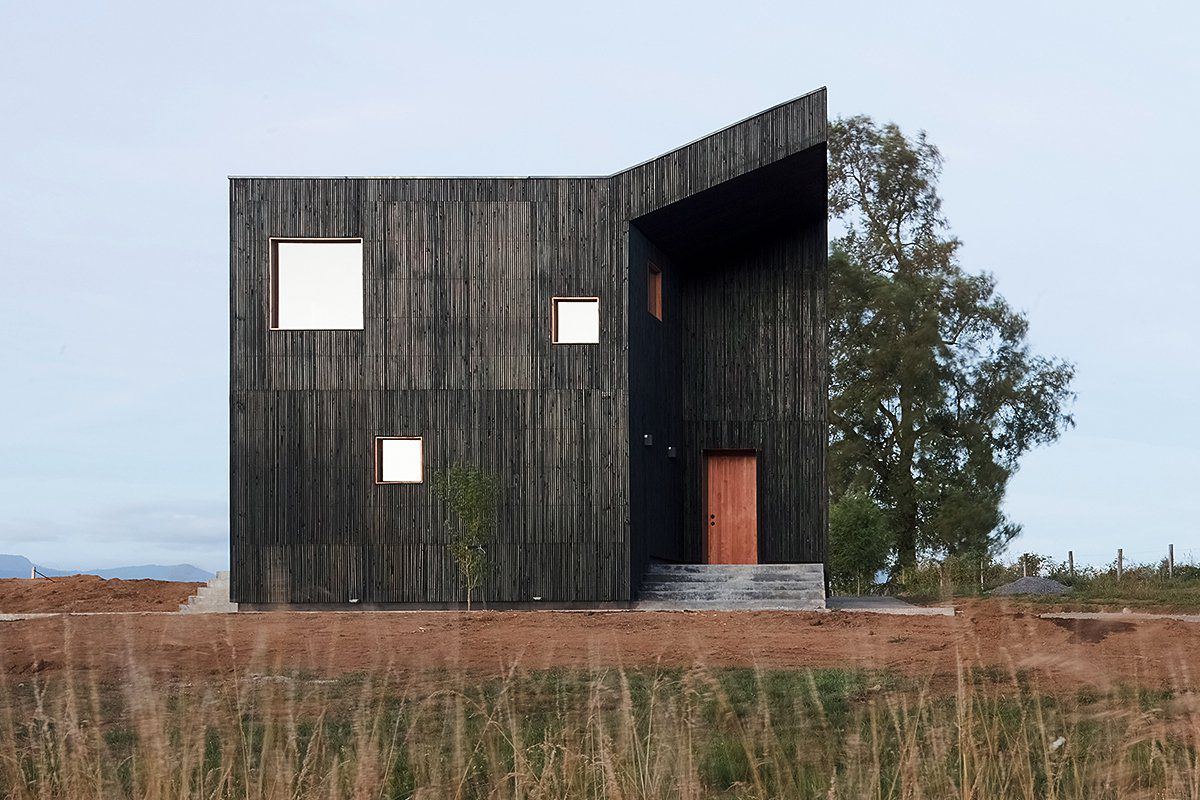 Simple blackened timber shed-like house with angled corner marking recessed entrance on flat site.