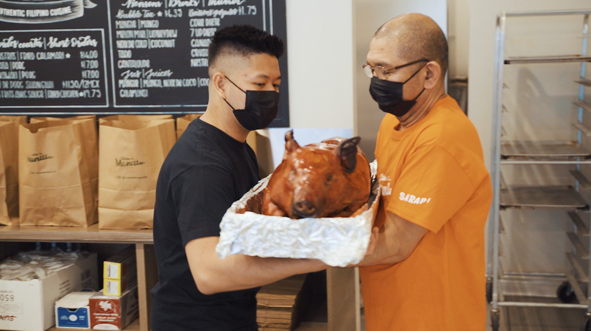 two men holding roasted pig