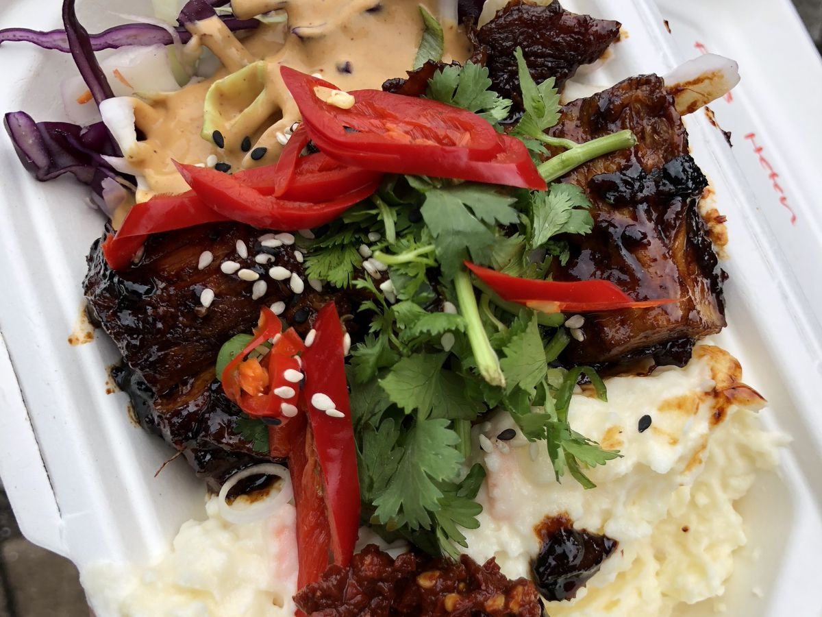 Pork belly with sambal, coleslaw and potato salad from street food stall Smokin' Lotus, one of London's best live fire restaurants