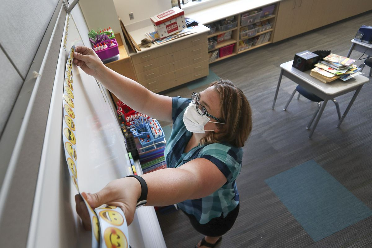 Third grade teacher Tiffany Rudelich puts magnetic smiley face strips on the white board in her classroom at the newly constructed Midvalley Elementary School, 217 E. 7800 South, in Midvale on Monday, Aug. 10, 2020.