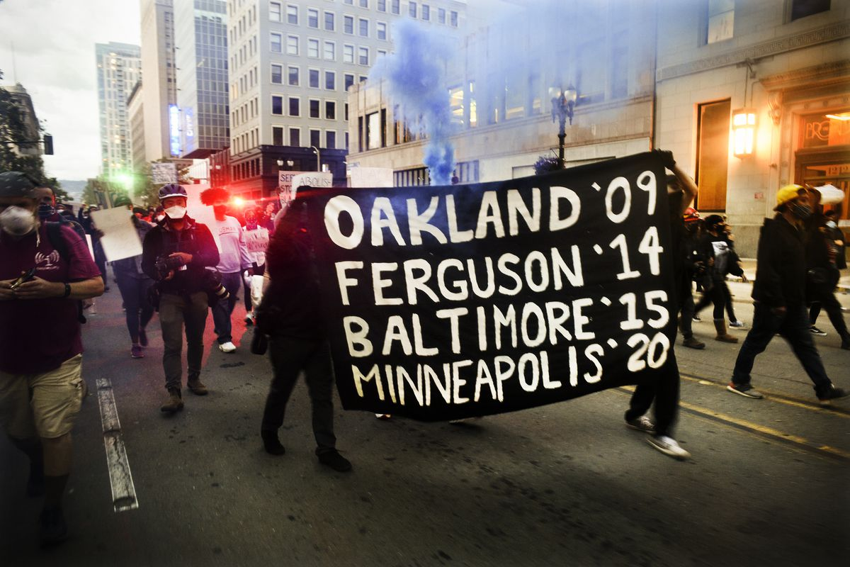 "The black banner, with white writing, reads, ""Oakland '09 Ferguson '14 Baltimore '15 Minneapolis '20."""
