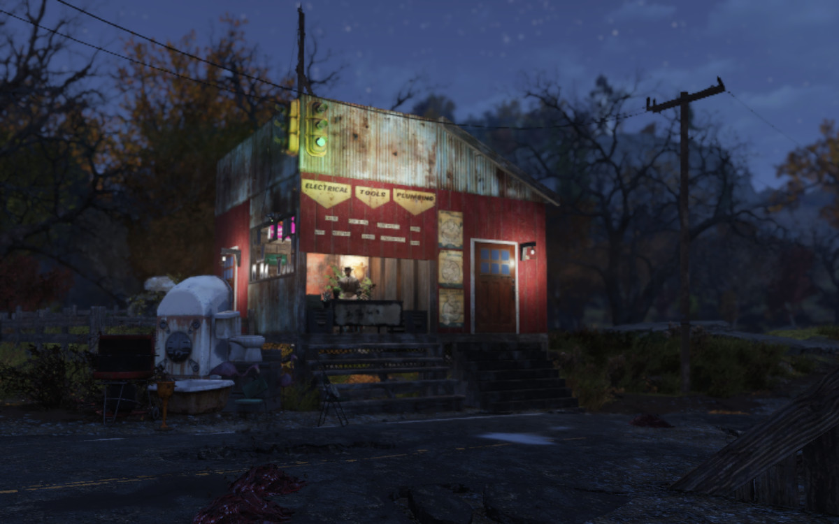 a roadside shop at night with a traffic light hanging in front of it in Fallout 76
