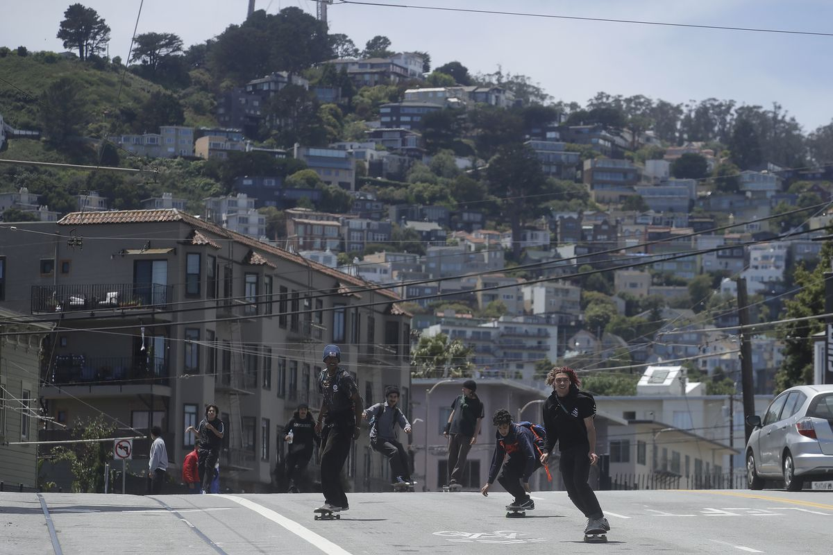 People on skateboards hurling down a street against a backdrop of hillside homes and green hillsides.
