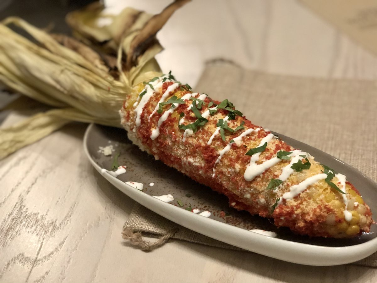 Grilled corn on the cob with charred husk pulled back and topped with chile, crema, and chopped peppers