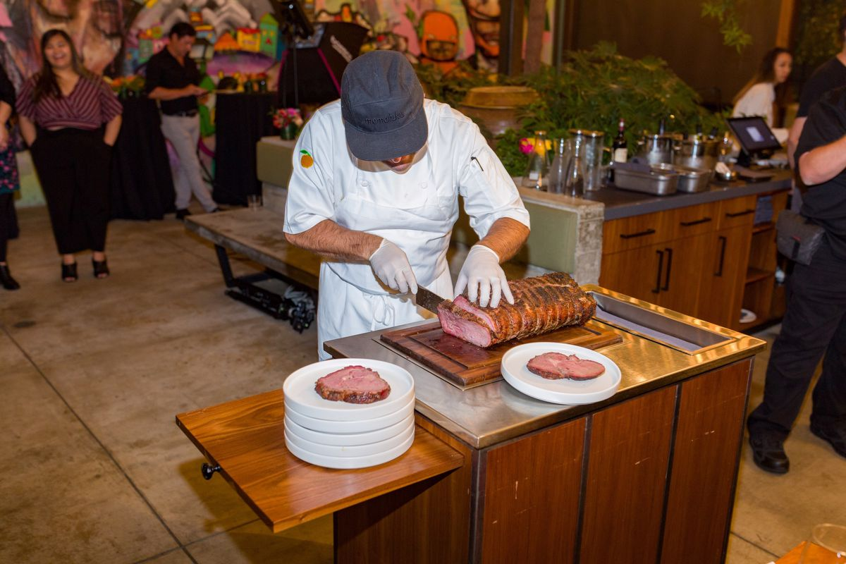 A chef carves prime rib on a table-side cart