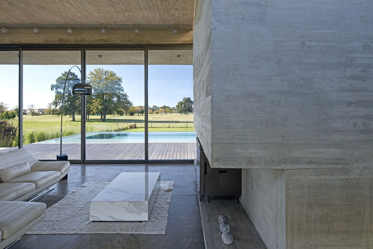 Living room built from concrete with glass wall overlooking pool.