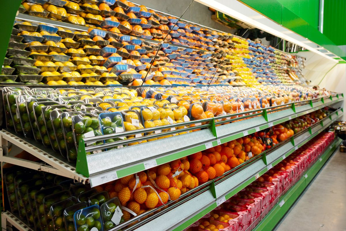 A refrigerated grocery store shelving unit with a mirrored top, stocked full of various citrus fruits.