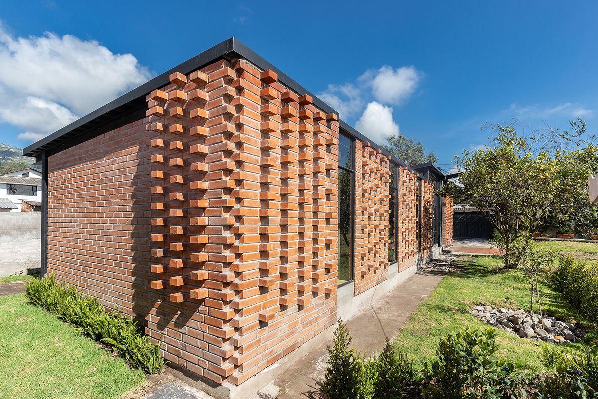 Brick house sitting on green lawn.