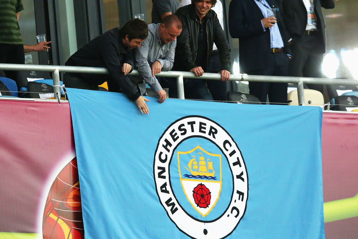 KIEV, UKRAINE - JUNE 15:  Musician Noel Gallagher (L) unravels a Manchester City flag ahead of the UEFA EURO 2012 group D match between Sweden and England at The Olympic Stadium on June 15, 2012 in Kiev, Ukraine.  (Photo by Alex Livesey/Getty Images)