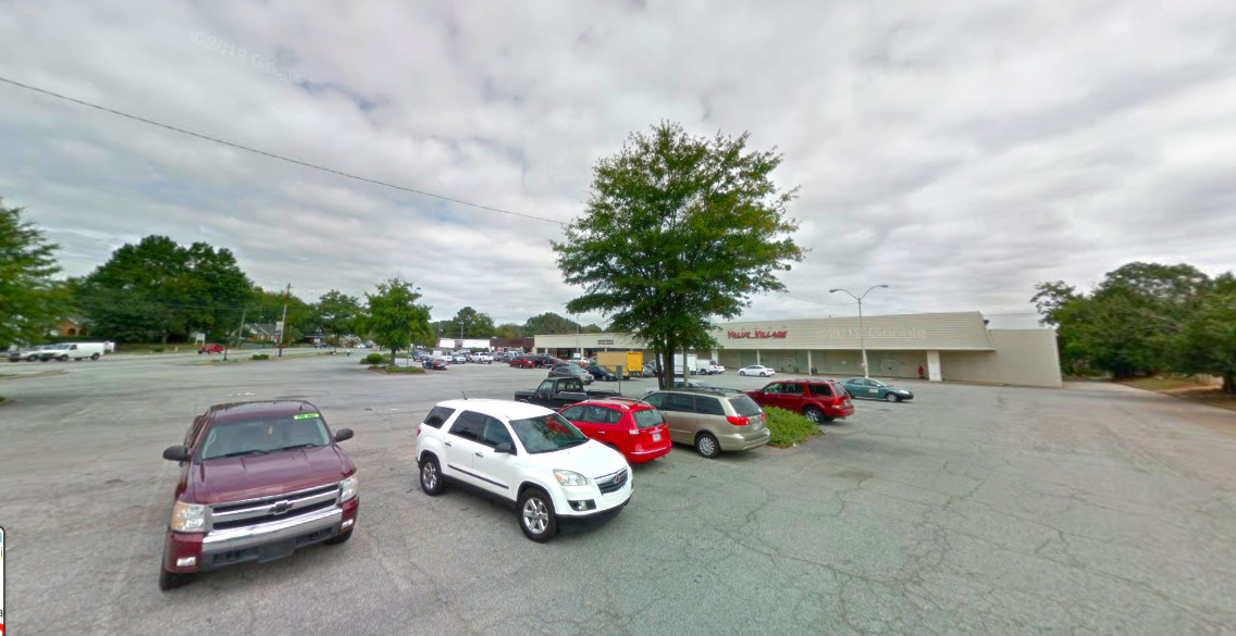 A photo showing an empty parking lot and old shopping center.