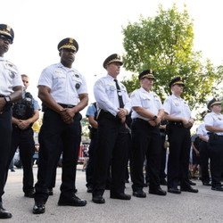 Police Officers bow their heads in prayer during a memorial and prayer service for fallen Officer Ella French outside the 22nd District Police Station Wednesday.