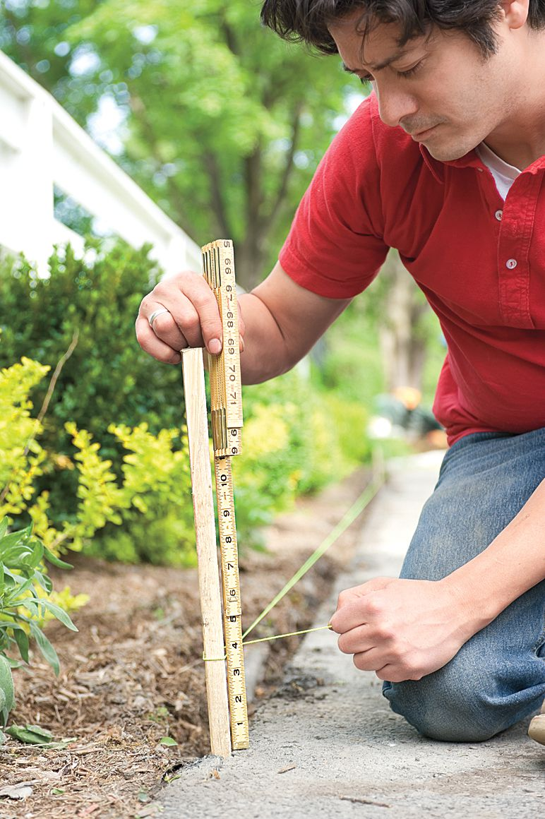 Man Drives Stake At End Of Trench To Level Line For Driveway Edging